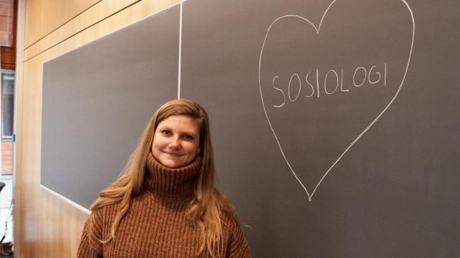 Foto av Marit Frydenlund foran tavle med skriften sosiologi inni et hjerte